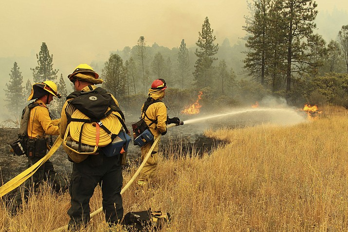 Firefighters from Yocha Dehe Fire Department work together to put out a grass fire Friday, Sept. 7, 2018, along Interstate 5 at Earl Sholes Memorial Bridge near Shasta-Trinity National Forest, Calif. (Hung T. Vu/The Record Searchlight via AP)