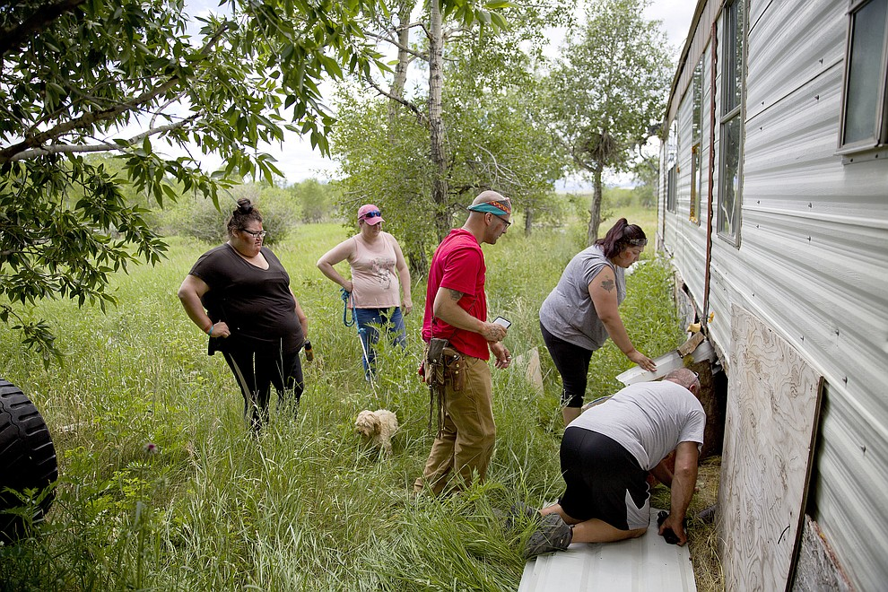 "Kimberly Loring, from left, Staci Salois, Randy Ortiz, Lissa Loring and George A. Hall, look for clues under a trailer during a search in Valier, Mont., for the Loring's sister and cousin, Ashley HeavyRunner Loring, who went missing in 2017 from the Blackfeet Indian Reservation, Wednesday, July 11, 2018. Lissa says Ashley's disappearance constantly weighs on her. ""All that plays in my head is where do we look? Who's going to tell us the next lead?"" (AP Photo/David Goldman)"