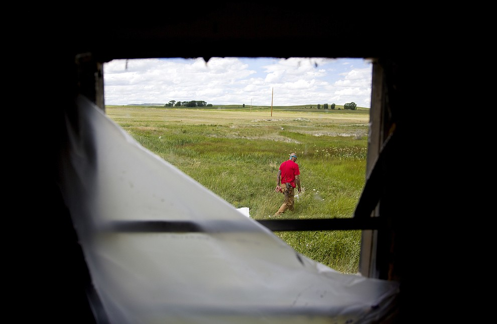 Randy Ortiz combs a field outside a trailer during a search for Ashley HeavyRunner Loring, who went missing from the Blackfeet Indian Reservation more than a year ago, in Valier, Mont., Wednesday, July 11, 2018. Ashley's cousins lived at the trailer, and there are reports it's among the last places she was seen. (AP Photo/David Goldman)