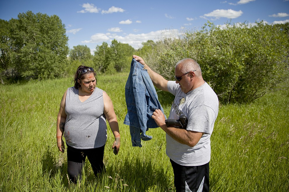 "George A. Hall, right, holds up a jacket found with Lissa Loring, during a search in Valier. Mont., for Loring's cousin, Ashley HeavyRunner Loring, who went missing last year from the Blackfeet Indian Reservation, Wednesday, July 11, 2018. ""We're following every rumor there is, even if it sounds ridiculous,"" Loring says. (AP Photo/David Goldman)"