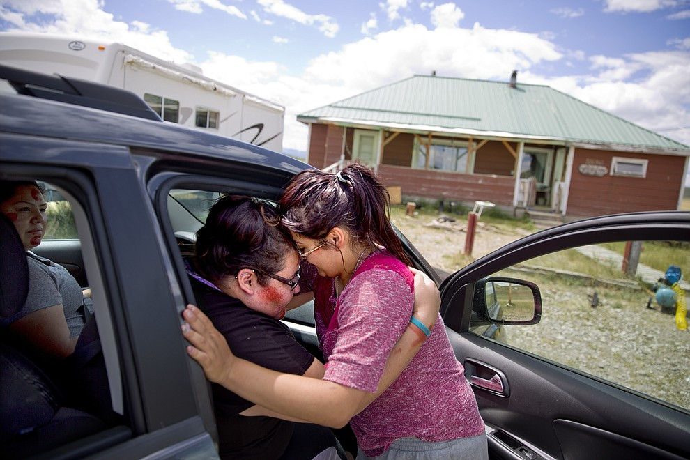 "Kimberly Loring, left, touches her forehead to her little sister, Jonnilyn, 17, as she says goodbye before heading out on a search for their missing sister Ashley with their cousin, Lissa Loring, left, outside their home on the Blackfeet Indian Reservation in Browning, Mont., Wednesday, July 11, 2018. ""I'm the older sister. I need to do this,"" says 24-year-old Kimberly. ""I don't want to search until I'm 80. But if I have to, I will."" (AP Photo/David Goldman)"