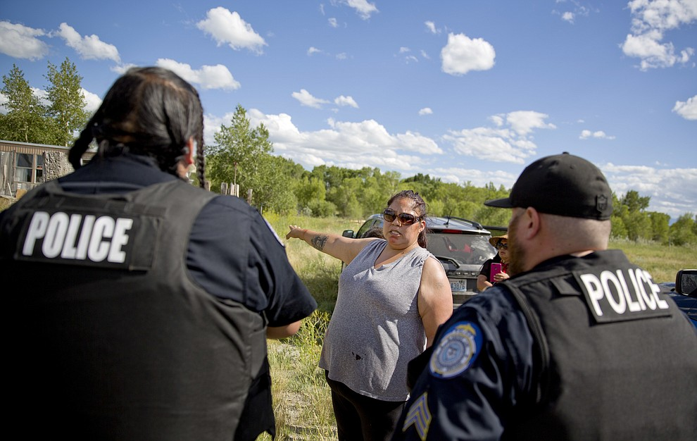 Lissa Loring points Blackfeet law enforcement officers to a trailer in Valier, Mont., where she believes clues have been found during a search for her cousin, Ashley HeavyRunner Loring, who went missing last year from the Blackfeet Indian Reservation, Wednesday, July 11, 2018. This search is motivated, in part, by the family's disappointment with the reservation police force_ a common sentiment for many relatives of missing Native Americans. (AP Photo/David Goldman)