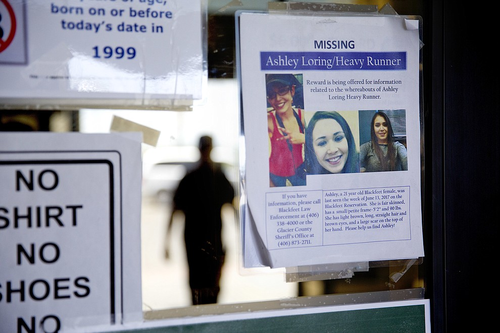 A missing poster for Ashley HeavyRunner Loring is posted to the entrance of a grocery store on the Blackfeet Indian Reservation in Browning, Mont., Thursday, July 12, 2018. At first, her relatives say, tribal police suggested Ashley was old enough to take off on her own. The Bureau of Indian Affairs and tribal police headed up the initial investigation. The FBI later took over. BIA spokeswoman Nedra Darling says 55 people have been interviewed and 38 searches conducted. (AP Photo/David Goldman)
