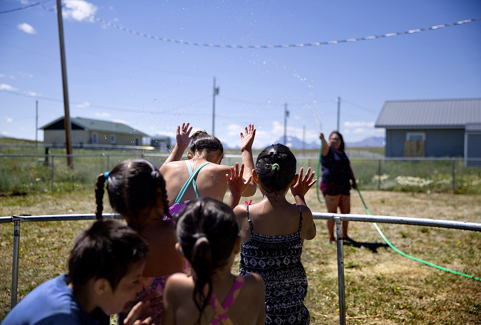 "Tyisha ArrowTop Knot, right, sprays her nieces and nephews with a garden hose while looking after them in the backyard of their home on the Blackfeet Indian Reservation in Browning, Mont., Thursday, July 12, 2018. ""We've always been a cautious family,"" she said of watching out for the children in light of recent disappearances of Native American women. ""The world is just getting worse."" (AP Photo/David Goldman)"