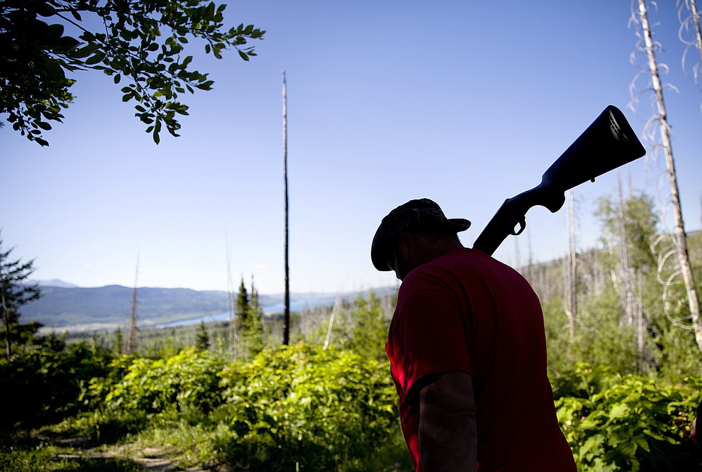 George A. Hall carries his shotgun as protection against bears while searching for Ashley HeavyRunner Loring in the mountains of the Blackfeet Indian Reservation in Babb, Mont., Thursday July 12, 2018. No one knows how many Native American women and girls go missing, but there's often a similar pattern once they do: A community outcry, a search and the offer of a reward. There may be a quick resolution. But often, there's frustration with tribal police and federal authorities, and a feeling many cases aren't handled urgently or thoroughly. (AP Photo/David Goldman)