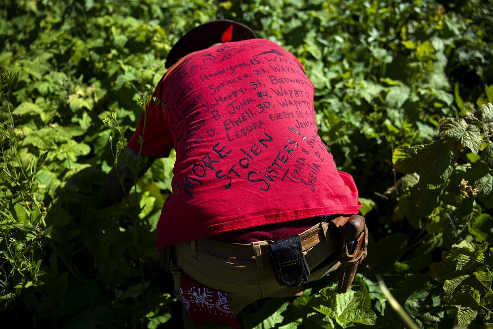 Randy Ortiz wears a shirt with the names of missing and murdered indigenous women as he searches for Ashley HeavyRunner Loring in the mountains of the Blackfeet Indian Reservation in Babb, Mont., Thursday July 12, 2018. On some reservations, Native American women are murdered at a rate more than 10 times the national average, and a third of all Native American women will be raped at some point, according to the Justice Department. (AP Photo/David Goldman)