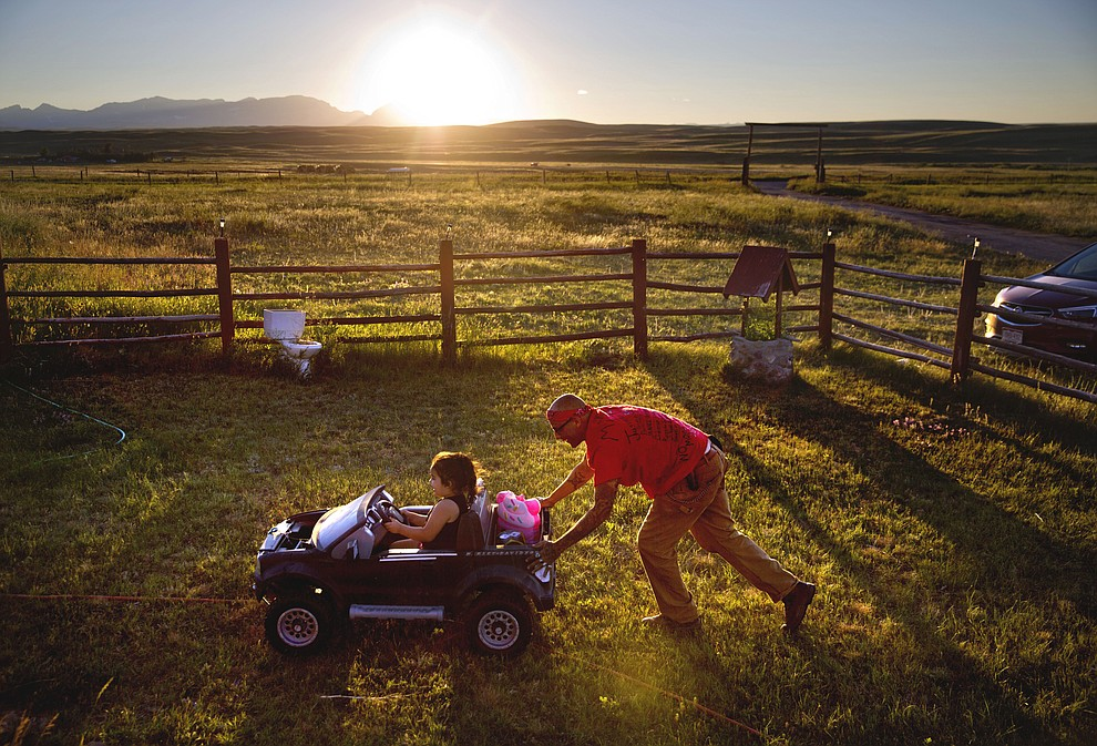 Randy Ortiz, right, pushes Ronnie Loring, 3, the cousin of Ashley HeavyRunner Loring, as they take a break from searching for her on the Blackfeet Indian Reservation in Browning, Mont., Thursday July 12, 2018. The family has logged about 40 searches but there's no way to cover a 1.5 million acre reservation, an expanse larger than Delaware. (AP Photo/David Goldman)