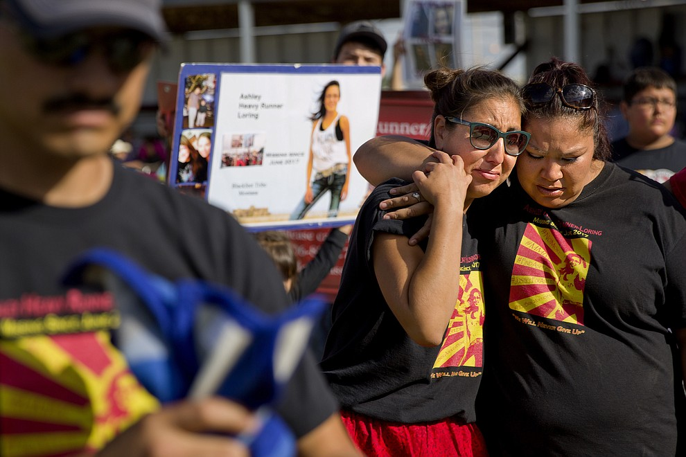"Jenna Loring, left, the aunt of Ashley HeavyRunner Loring, cries with her cousin, Lissa Loring, during a traditional blanket dance before the crowd at the North American Indian Days celebration on the Blackfeet Indian Reservation in Browning, Mont., Saturday, July 14, 2018. The 'dance' was held to raise awareness and funds for Ashley's search. With just about 1,000 residents on the reservation, many folks are related and secrets have a way of spilling out. ""There's always somebody talking,"" says Lissa, ""and it seems like to us since she disappeared, everybody got quiet. I don't know if they're scared, but so are we. That's why we need people to speak up."" (AP Photo/David Goldman)"