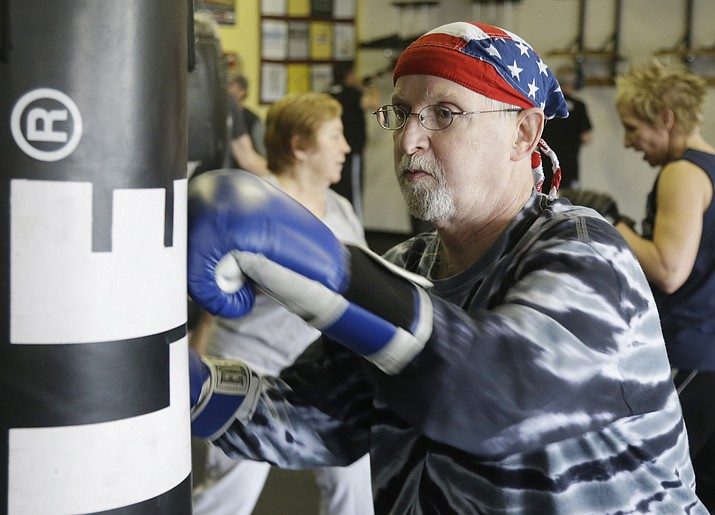 Dave Beery hits a heavy bag during a workout March 19, 2013, at Rock Steady Boxing in Indianapolis. Activities that challenge the heart and lungs, such as boxing, are important for those living with Parkinson's disease, says Brian Shaw, OTR and Director of Therapy Operations at Mountain Valley Regional Rehabilitation Hospital.