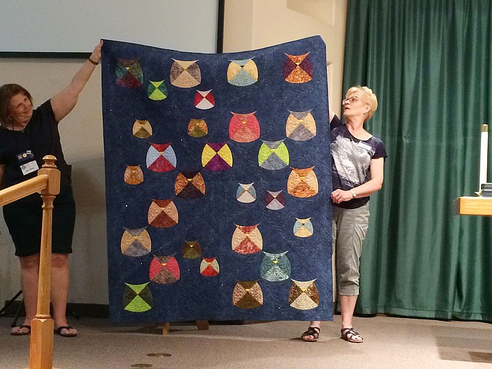 Peggy Nehring, not pictured, gets help from members of the Lonesome Valley Quilt Guild to show one of her many quilts at the Guild's Sept. 10 meeting. Nehring is an instructor at Quilt 'n Sew in Prescott Valley. Her Parliament of Owls quilt includes Winston, Clementine and children, Hedwig, and parliament members who served with Churchill. The sparkles, representing stars, are crystals attached to the fabric. (Sue Tone/Tribune)