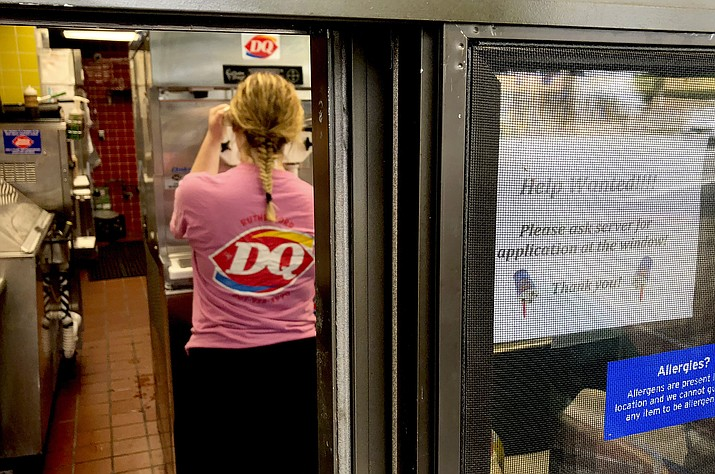 "A woman prepares a cup of ice cream behind a ""Help Wanted"" sign at a Dairy Queen restaurant in Rutherford, New Jersey, Aug. 19, 2018. (Ted Shaffrey/AP Photo, file)"