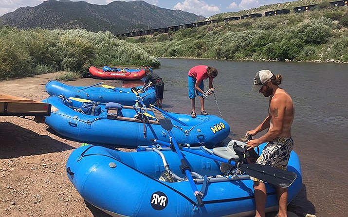 Jordan Poythress (right) prepares his raft to go down the Arkansas River near Cañon City. (Ali Budner/KRCC)