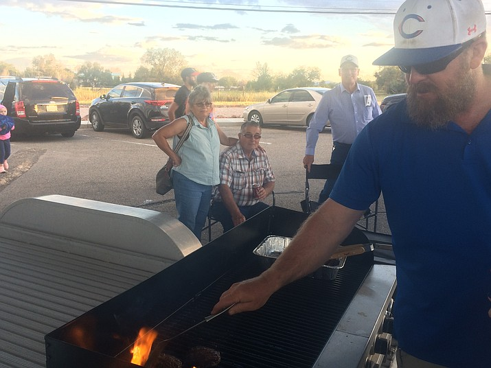 Jim Wilmington grills burgers at a tailgate party in front of Chino Valley High School prior to the Cougars' home opener Friday, Sept. 7. The tailgater was sponsored by the football booster club for the home opener. Future tailgaters include Sept. 28 (versus Kingman Academy) for Youth Night, and Oct. 26 (versus Northwest Christian) for Senior Night. On Sept. 7, Chino Valley battled Camp Verde for the Bronze Boot, which the Cougars retained again — in a 42-0 effort. (Jason Wheeler/Review)
