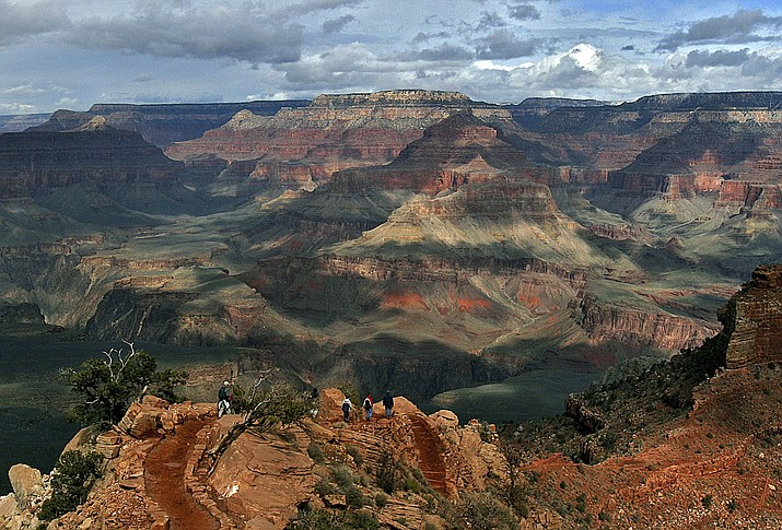 The North Rim of the Grand Canyon is in the background as tourists hike along the South Rim in Grand Canyon, Arizona. Lower snowfall in recent years at the North Rim is prompting tourism officials to expand the visiting season for tourists. (Rick Hossman, AP Photo File)