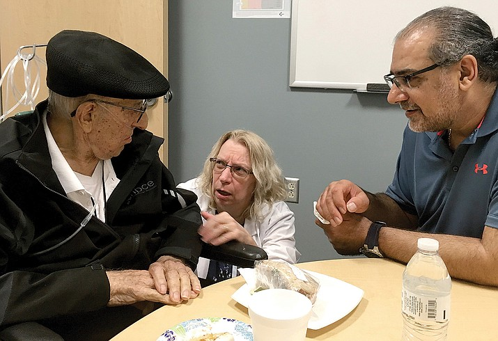 The Rev. John Sabbagh, left, and his son Ebby Sabbagh talk with nurse practitioner Kim O'Riley on Friday, Sept. 7, 2018 in Gilbert. Rev. Sabbagh his son are celebrating one year of going strong since the elder Sabbagh received a crucial stem-cell transplant. (Terry Tang/AP Photo)
