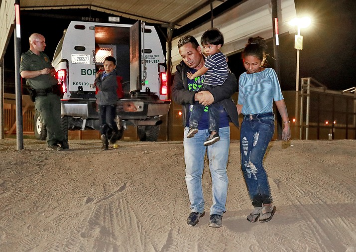 A Honduran man carries his 3-year-old son as his daughter and other son follow to a transport vehicle after being detained by U.S. Customs and Border Patrol agents July 18, 2018, in San Luis, Ariz. Border arrests figures for August 2018, are the latest reminder of how crossings have shifted over the last decade from predominantly Mexican men to Central American families and children. (Matt York/AP Photo File)