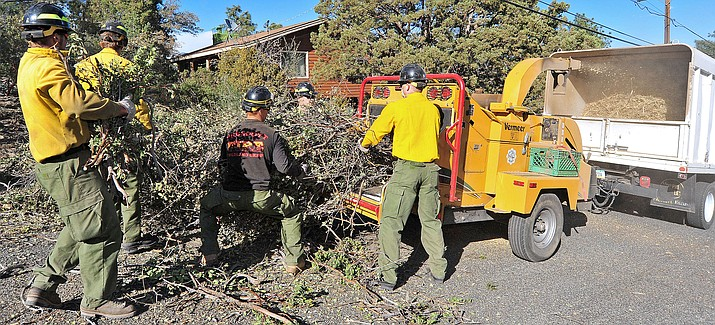 Members of the Prescott Fire Department's Wildland Brush Crew load limbs, leaves, and debris into a chipper on Vista Ridge Road in 2014. (Courier file photo)