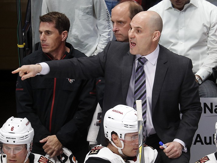 FILE - In this Dec. 27, 2017, file photo, Arizona Coyotes head coach Rick Tocchet directs his team during the third period of an NHL hockey game against the Colorado Avalanche in Denver. The Coyotes enter camp with optimism after finishing last season strong and making moves during the offseason to upgrade their roster. They know what coach Tocchet expects and his system. (David Zalubowski/AP, file)