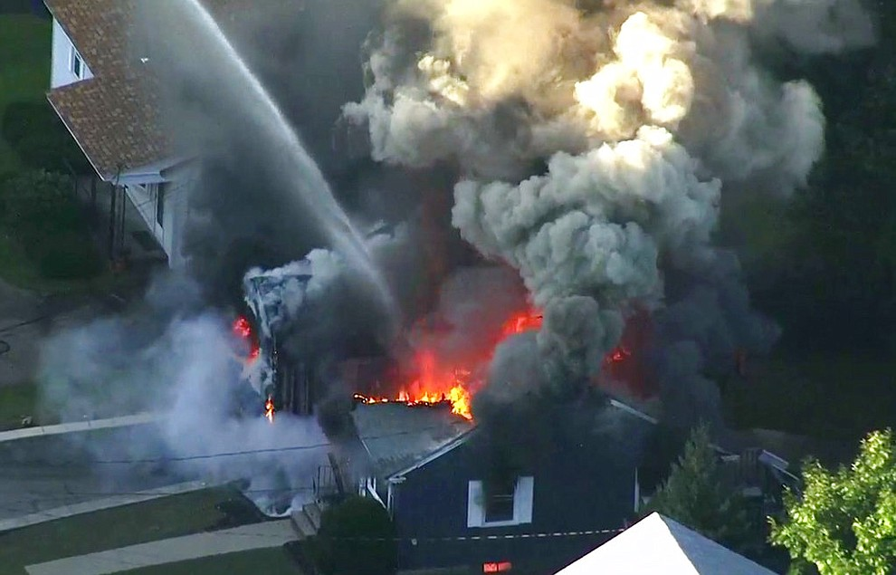 In this image take from video provided by WCVB in Boston, flames consume the roof of a home in Lawrence, Mass, a suburb of Boston, Thursday, Sept. 13, 2018. A series of gas explosions killed a teenager, injured at least 10 other people and ignited fires in at least 39 homes in three communities north of Boston, forcing entire neighborhoods to evacuate as crews scrambled to fight the flames and shut off the gas. (WCVB via AP)