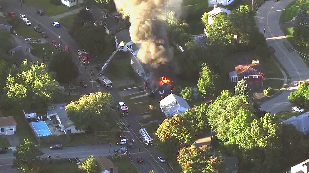 In this image take from video provided by WCVB in Boston, firefighters battle a raging house fire in Lawrence, Mass, a suburb of Boston, Thursday, Sept. 13, 2018. Emergency crews responded to what they believe is a series of gas explosions that have damaged homes across three communities north of Boston. (WCVB via AP)