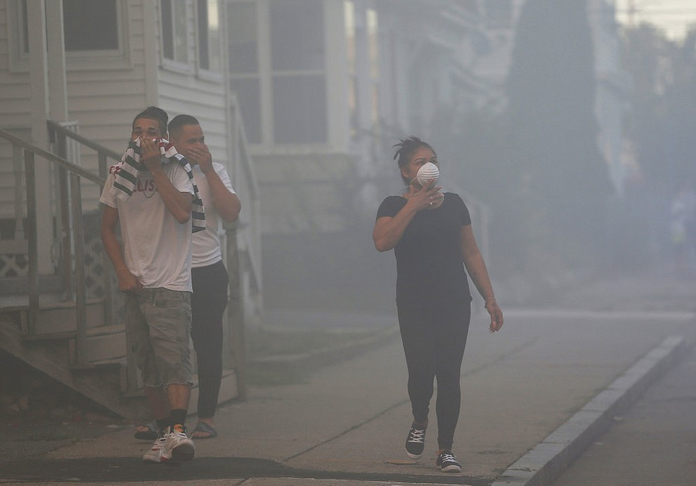 People cover their faces to protect themselves from heavy smoke from a fire on Bowdoin Street in Lawrence, Mass., Thursday, Sept. 13, 2018. The company that owns Columbia Gas says its crews are performing safety checks after a series of fires and explosions erupted in three communities north of Boston. (Jessica Rinaldi/The Boston Globe via AP)