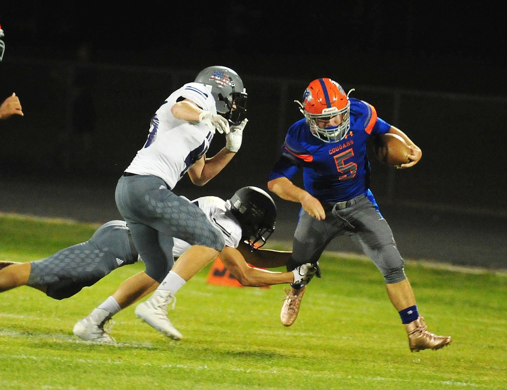 Chino Valley's Mikey Paulus breaks a tackle as the Cougars host Arizona College Prep Friday, Sept. 14, 2018. (Les Stukenberg/Courier)