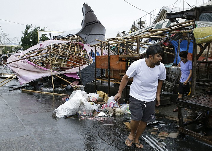 A resident walks past damaged stalls at a public market as Typhoon Mangkhut barreled across Tuguegarao city in Cagayan province, northeastern Philippines on Saturday, Sept. 15, 2018. The typhoon slammed into the Philippines northeastern coast early Saturday, it's ferocious winds and blinding rain ripping off tin roof sheets and knocking out power, and plowed through the agricultural region at the start of the onslaught. (Aaron Favila/AP Photo)