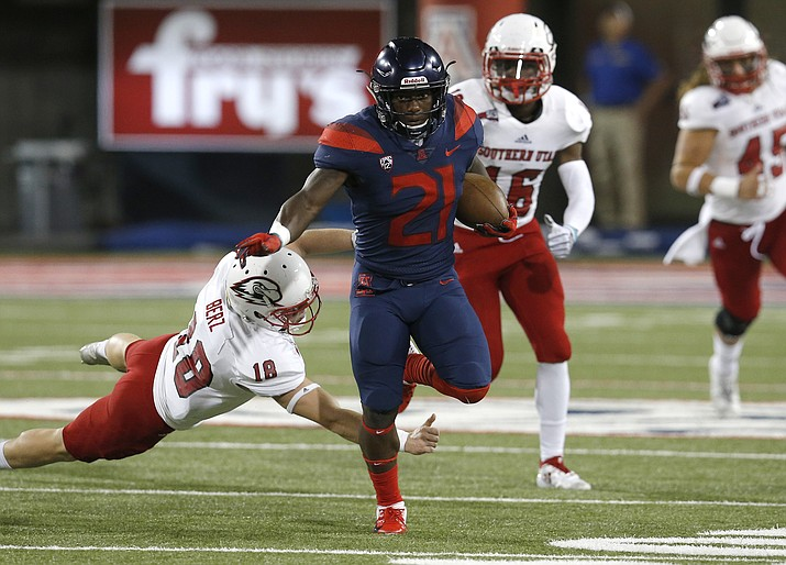 Arizona running back J.J. Taylor (21) breaks the tackle from Southern Utah place kicker Manny Berz (18) and scores a touchdown on a kickoff in the first half Saturday, Sept. 15, 2018, in Tucson. (AP photo)