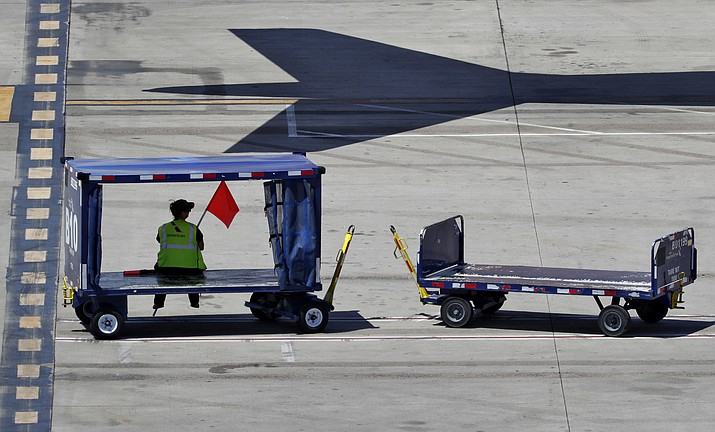 A member of the American Airlines grounds crews seeks shelter on an empty luggage cart Wednesday, July 25, 2018 at Sky Harbor International Airport in Phoenix. Police say a terminal at the Phoenix airport has been re-opened after an unattended rental car left in a curb lane prompted a security scare Sunday, Sept. 16, 2018. (Matt York/AP, file)