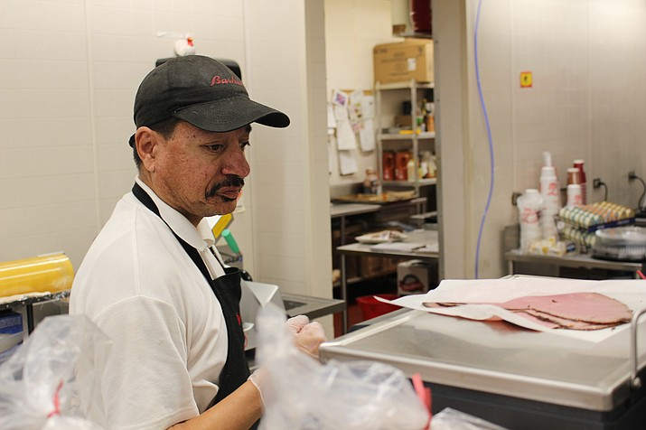 Tony Veloz weighs a few slices of roast beef at Bashas' deli on Friday. Bashas' has given a few suggestions for turning school lunches into tastier, healthier choices for their kids. (Photo by Hubble Ray Smith/Daily Miner)