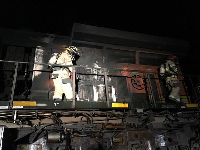 Central Arizona Fire and Medical Authority personnel inspect a train that was passing through Paulden early Sunday morning when one of its engines caught fire and firefighters were called out to extinguish it.