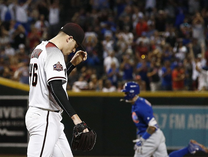 Arizona Diamondbacks starting pitcher Patrick Corbin (46) pauses on the mound after giving up a two-run home run to Chicago Cubs' Javier Baez, right, during the sixth inning Monday, Sept. 17, 2018, in Phoenix. (Ross D. Franklin/AP)