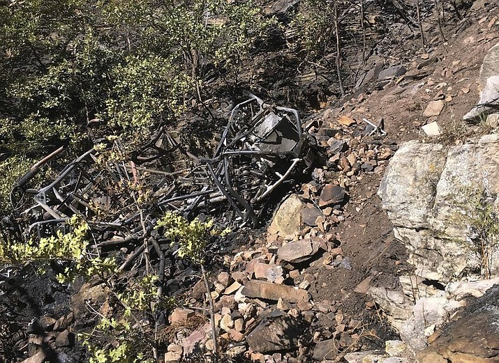 This photo provided by the Coconino County Sheriff's Office, posted Monday, Sept. 17, 2018, shows the burned wreckage of an ATV, found at the bottom of a 400-foot cliff, in the Coconino National Forest. Authorities say the bodies of four men killed in the fiery crash have been recovered. Coconino County Sheriff's officials say a 10-acre fire and rugged terrain made it difficult for rescuers in the Blue Ridge area to get to the site of Saturday's crash. (Coconino County Sheriff's Office photo)