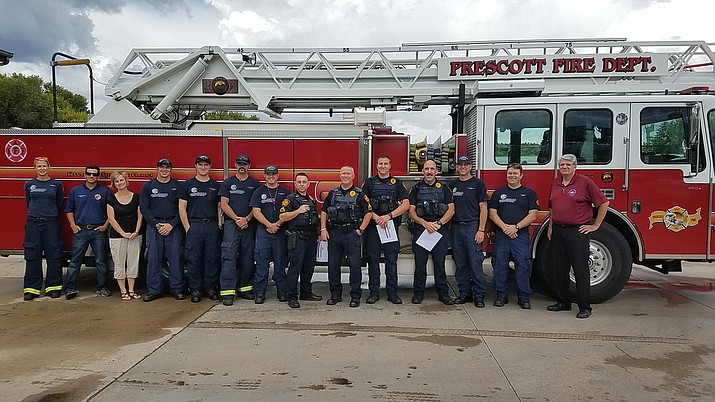 The Prescott Fire Department awards several Prescott Police officers with certificates for the aid the officers rendered during an EMS call in August. (Prescott Fire Department/Courtesy)