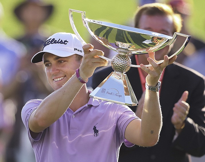 In this Sept. 24, 2017, file photo, Justin Thomas holds the trophy after winning the Fedex Cup after the Tour Championship golf tournament at East Lake Golf Club in Atlanta. The bonus pool for the PGA Tour season doubles next year to $70 million in a revamped system that pays $15 million to the FedEx Cup champion. (Curtis Compton/Atlanta Journal-Constitution via AP, file)