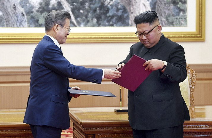 South Korean President Moon Jae-in, left, and North Korean leader Kim Jong Un exchange the documents after signing at the Paekhwawon State Guesthouse in Pyongyang, North Korea, Wednesday, Sept. 19, 2018. Moon and Kim announced a sweeping set of agreements after their second day of talks in Pyongyang on Wednesday that included a promise by Kim to permanently dismantle the North's main nuclear complex if the United States takes corresponding measures, the acceptance of international inspectors to monitor the closing of a key missile test site and launch pad and a vow to work together to host the Summer Olympics in 2032.(Pyongyang Press Corps Pool via AP)