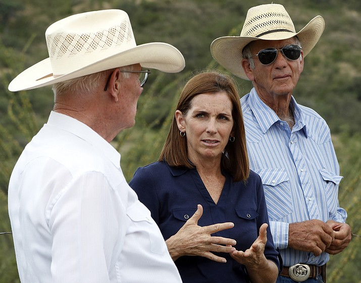 In this Aug. 22, 2018, file photo, U.S. Senatorial candidate U.S. Rep. Martha McSally, R-Ariz., stands at the international border with Mexico, with ranchers Jim Chilton, left, and Tom Kay, right, south of Arivaca, Ariz. For a decade, the fight against illegal immigration has helped Republicans win every statewide election in Arizona. Now, in what's shaping up to be a difficult November for the GOP, they're counting on it helping extend their winning streak in Arizona and maintain their hold on the U.S. Senate. (Matt York/AP, file)