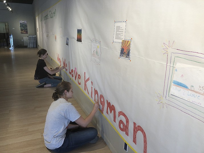 Alexandra Rice, front, and Anna Fox Ryan work on a banner for tonight's event at Kingman Center for the Arts. (Courtesy photo)