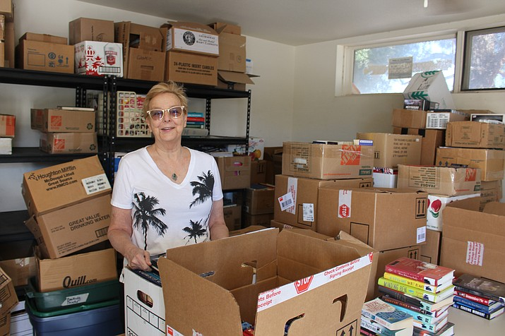 Yvonne Decker, treasurer of Friends of the Kingman Library, sorts through boxes of donated books and materials for the book sale Friday and Saturday to support library programs. (Photo by Hubble Ray Smith/Daily Miner)