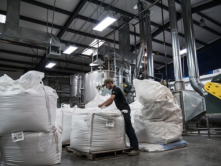 """Yann Raymond checks bags of malt barley ready for local brewers. Although Sinagua malt barley is more expensive, brewers are attracted to its message of """"naturalism and conservation,"""" malt house owner Chip Norton said. (Jordan Evans, Cronkite News/Courtesy)"""