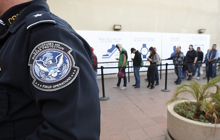 "In this Dec. 10, 2015, file photo, pedestrians crossing from Mexico into the United States at the Otay Mesa Port of Entry wait in line in San Diego. The Trump administration is proposing rules that could deny green cards to immigrants if they use Medicaid, food stamps, housing vouchers and other forms of public assistance. The Department of Homeland Security said Saturday, Sept. 22, 2018, that current and past receipt of certain public benefits above thresholds will be considered ""a heavily weighed negative factor"" in granting green cards as well as temporary visas. (Denis Poroy/AP, File)"
