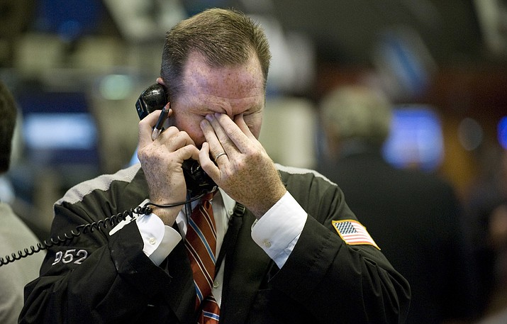 In this Sept. 17, 2008, file photo trader Christopher Crotty rubs his eyes as he works on the floor of the New York Stock Exchange. Home prices had sunk, and foreclosure notices began arriving. Layoffs began to spike. Tremors intensified as Lehman Brothers, a titan of Wall Street, slid into bankruptcy on Sept. 15, 2008. The financial crisis touched off the worst recession since the 1930s Great Depression. (Richard Drew/AP, File)