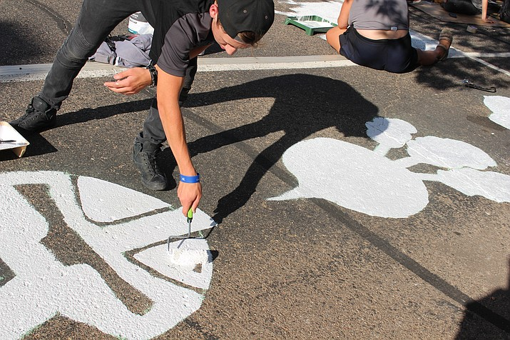 """Seth Fields painted his parking space Thursday with the help of his family. He paid homage to the show """"The Office."""" (Photo by Vanessa Espinoza/Daily Miner)"""