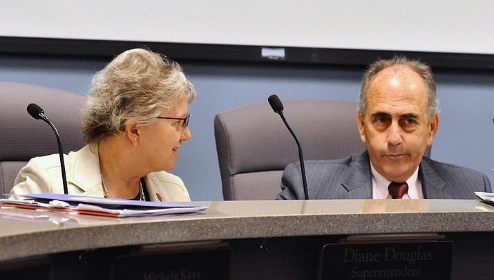 State schools chief Diane Douglas and Lucas Narducci, president of the state Board of Education, chat ahead of Monday's board meeting to discuss revamping science and social studies standards. (Capitol Media Services photo by Howard Fischer)
