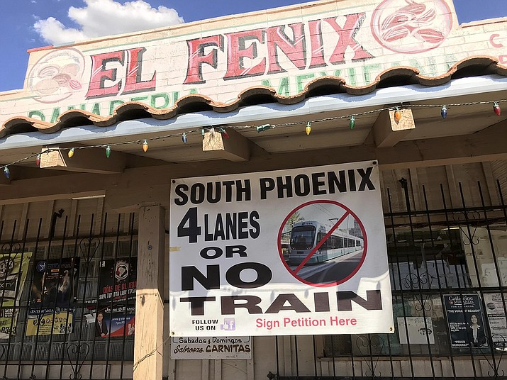 A local business displays a protest sign of the proposed extension of the light rail system along Central Avenue, in Phoenix, on Wednesday, Sept. 5, 2018. The proposed extension of Phoenix's light-rail system into the city's poorest neighborhood is running into eleventh-hour opposition from some business owners in the Hispanic and black community.(Anita Snow/AP)