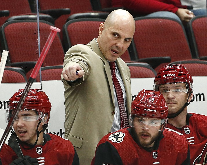 In this Sept. 18, 2018, file photo, Arizona Coyotes head coach Rick Tocchet, top, talks with Christian Fischer, right, Alex Galchenyuk (17) and Clayton Keller, left, during the first period of an NHL preseason hockey game against the Los Angeles Kings, in Glendale. (Ross D. Franklin/AP, file)