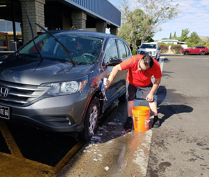 Armando Rodarte, plant manager of the Prescott Valley Printing Facility, washes a vehicle Saturday, Sept. 22, during the Courier Cares Car Wash. (Courier photo)