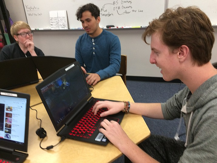 """Prescott High School senior Jack Ramsey plays the first eSports game at the school, """"League of Legends,"""" under supervision of Coach Marco DiMaria. Fellow team members sophomore Tim Demand and senior Joseph Perez tune into the game. (Nanci Hutson/Courier)"""