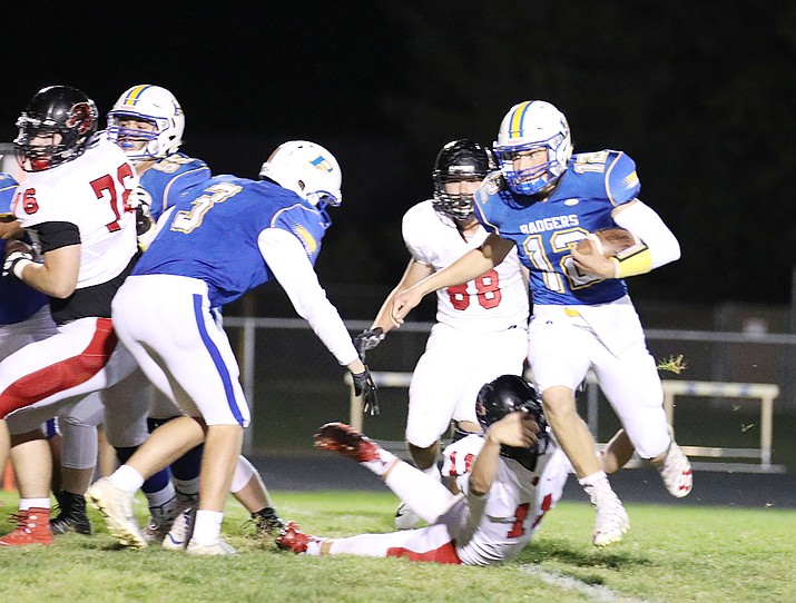 Prescott quarterback Austin Clark (12) avoids a tackler as the Badgers host Coconino on Friday, Sept. 28, 2018, in Prescott. Despite losing Clark to injury in the second half, Prescott beat the Panthers 28-16. (Jim Clark/Courtesy)
