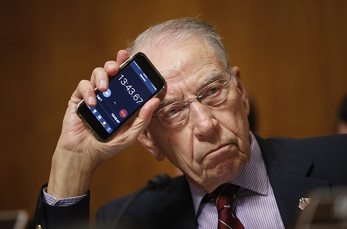 Senate Judiciary Committee Chairman Chuck Grassley of Iowa holds up a timer on a smartphone to show Sen. Cory Booker, D-N.J., how long he has been speaking for during a Senate Judiciary Committee hearing on Supreme Court nominee Judge Brett Kavanaugh, Friday, Sept. 28, 2018, on Capitol Hill in Washington. (Pablo Martinez Monsivais/AP)